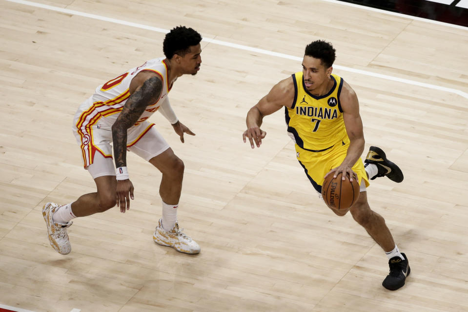Indiana Pacers guard Malcolm Brogdon (7) tries to drive around Atlanta Hawks forward John Collins (20) during the fourth quarter of an NBA basketball game Saturday, Feb. 13, 2021, in Atlanta. (AP Photo/Butch Dill)