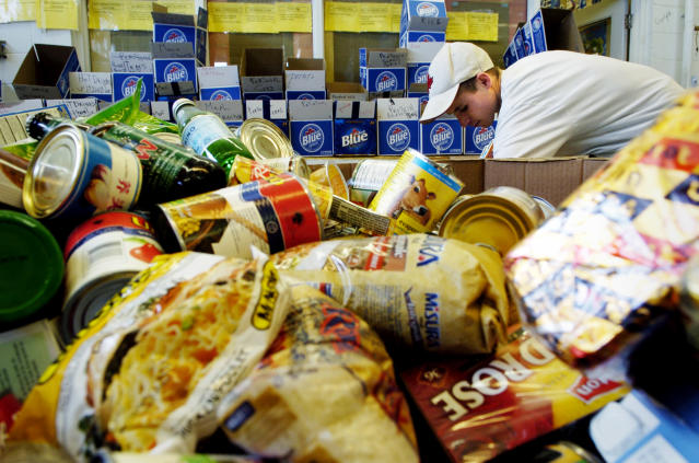 Ryan Hauck a worker at the North York Food Bank sorts through a box of items. (Photo by Carlos Osorio/Toronto Star via Getty Images)