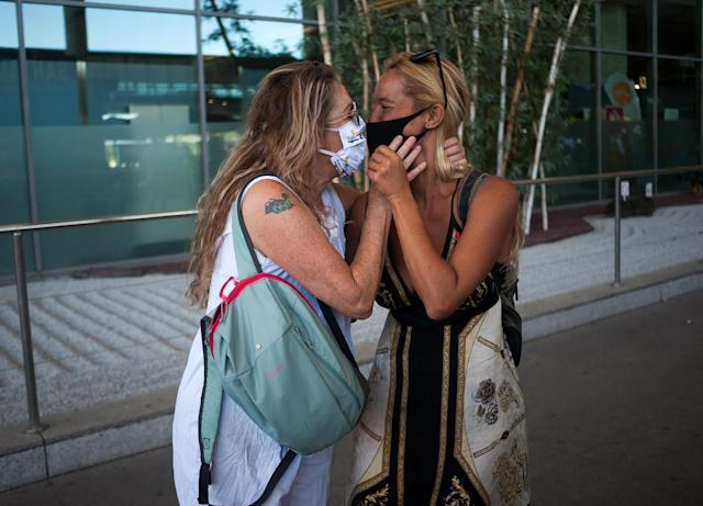 A mother and her daughter wearing face masks kiss at Malaga-Costa del Sol airport after Spain reopened its borders. (PA)