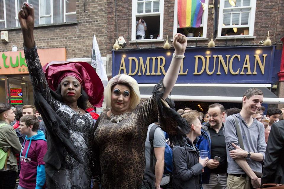 Photo of people gathering outside the Admiral Duncan pub in Old Compton Street in the Soho, which was attacked with a nail bomb on April 30, 1999, to remember the victims of the Orlando massacre, on June 13, 2016.