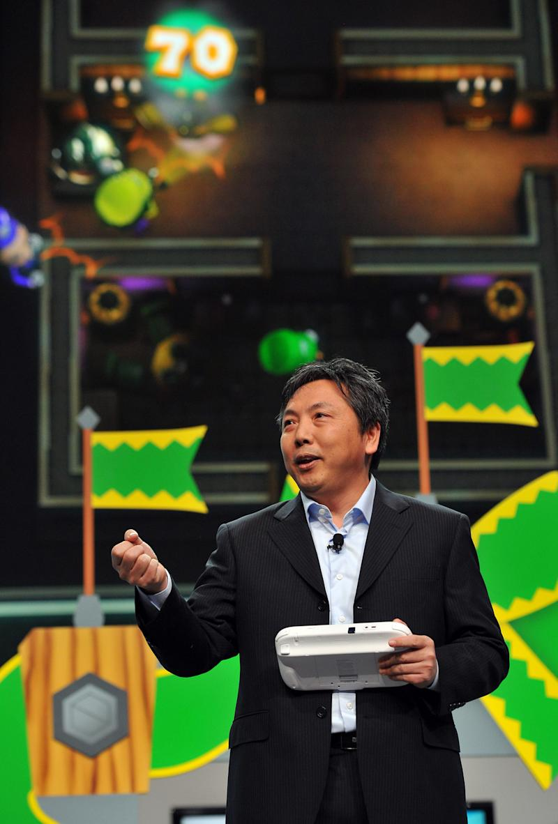 """FILE - In this June 5, 2012 publicity file photo provided by Nintendo of America, Katsuya Eguchi, Producer of Software Development for Nintendo, shows off """"Luigi's Ghost Mansion,"""" one of 12 attractions in Nintendo Land, an upcoming game for the new Wii U home console, during the Nintendo All-Access Presentation at E3 2012 in Los Angeles. The Wii U GamePad controller makes asymmetric gameplay possible by allowing for multiple experiences in the same game at the same time. (AP Photo/Nintendo of America, Vince Bucci, File)"""