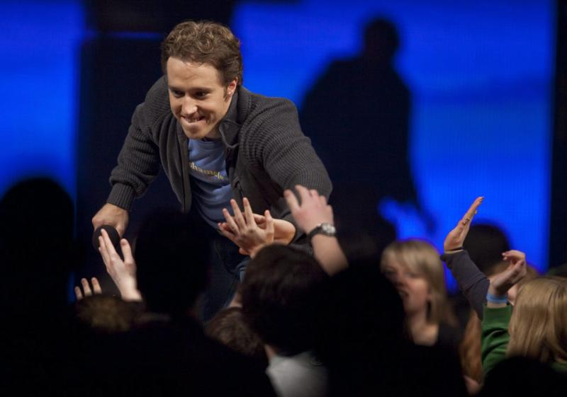 Craig Kielburger reaches down to touch the upraised hands of audience members.