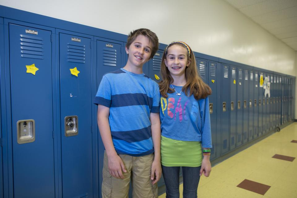 In this Thursday, June 6, 2013 photo, Evan Prendergast, left, and his twin sister, Olivia, one of the twenty-four sets of twins from Highcrest Middle School in Wilmette, Ill., pose for a portrait at the school. The group is attempting to break a Guinness World record for the amount of twins in one grade which is currently 16 sets. (AP Photo/Scott Eisen)