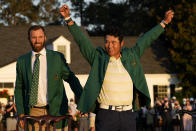 Hideki Matsuyama, of Japan, puts on the champion's green jacket after winning the Masters golf tournament as Dustin Johnson watches on Sunday, April 11, 2021, in Augusta, Ga. (AP Photo/David J. Phillip)