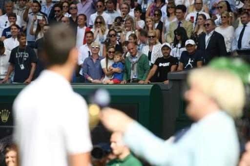 Family affair: Djokovic looks at his wife Jelena and son Stefan