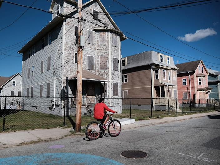 Homes are shown boarded up in Providence, Rhode Island. Someone in a red hoodie rides a bike past the houses.