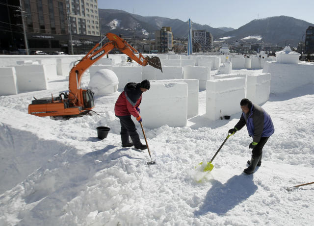 Workers move snow as they work on a large ice sculpture at the PyeongChang Olympic Plaza as preparations continue for the 2018 Winter Olympics. (AP)
