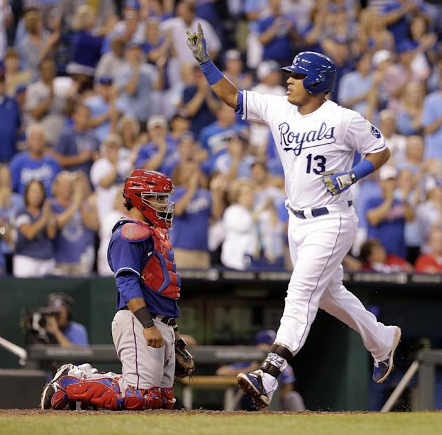 Kansas City Royals' Salvador Perez (13) runs past Texas Rangers catcher Tomas Telis after hitting a two-run home run during the third inning of a baseball game Monday, Sept. 1, 2014, in Kansas City, Mo. (AP Photo/Charlie Riedel)