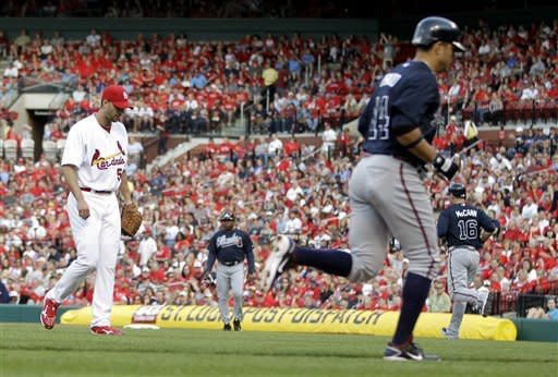 Atlanta Braves' Martin Prado (14) jogs in to score after St. Louis Cardinals' Adam Wainwright, left, walked Brian McCann (16) with the bases loaded during the first inning of a baseball game on Saturday, May 12, 2012, in St. Louis. (AP Photo/Jeff Roberson)