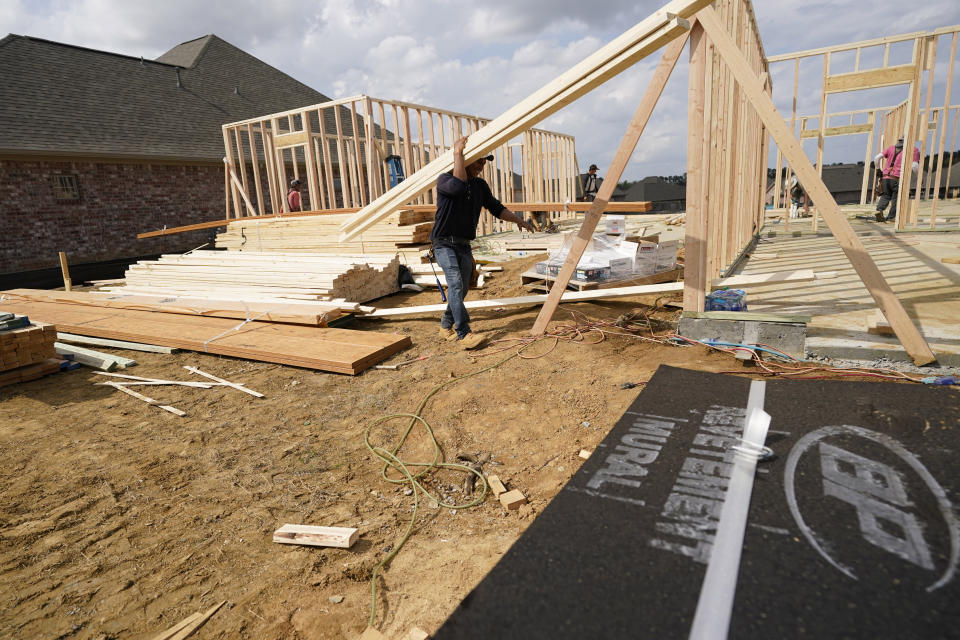 In this March 16, 2021 photo, a workman carries beamS at a new housing site in Madison County, Miss. Rising costs and shortages of building materials and labor are rippling across the homebuilding industry, which accounted for nearly 12% of all U.S. home sales in July. Construction delays are common, prompting many builders to pump the brakes on the number of new homes they put up for sale. As building a new home gets more expensive, some of those costs are passed along to buyers. (AP Photo/Rogelio V. Solis)
