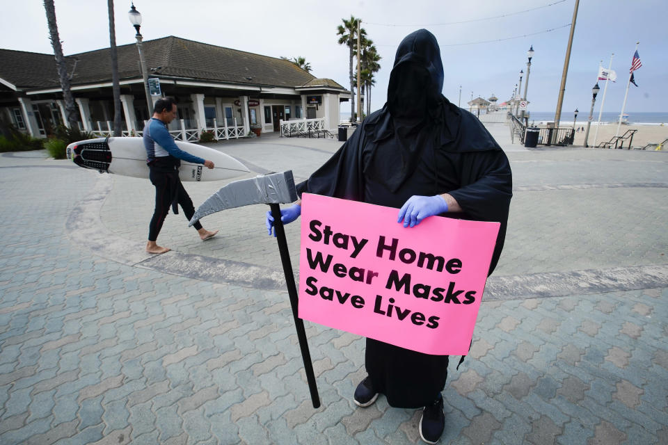 FILE - In this May 8, 2020, file photo, Spencer Kelly, dressed as the grim reaper, demonstrates in favor of the stay-at-home order during the coronavirus pandemic at the pier in Huntington Beach, Calif. Now, in early May 2021, California has the lowest case rate in the country. (AP Photo/Chris Carlson, File)
