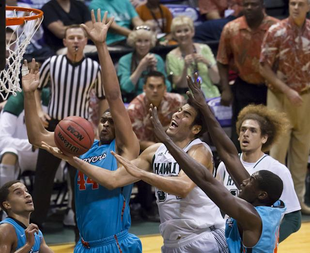 Hawaii forward Christian Standhardinger (34) reacts to being fouled by Oregon State forward Devon Collier, top left, as Hawaii forward Isaac Fotu, right back, and Oregon State forward Daniel Gomis. right front, watch during the second half of an NCAA college basketball game at the Diamond Head Classic on Wednesday, Dec. 25, 2013, in Honolulu. Hawaii won 79-73. (AP Photo/Eugene Tanner)