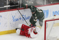 Minnesota Wild's Luke Kunin, right, sends Detroit Red Wings' Carson Soucy to the ice in the first period of an NHL hockey game Wednesday, Jan. 22, 2020, in St. Paul, Minn. (AP Photo/Jim Mone)