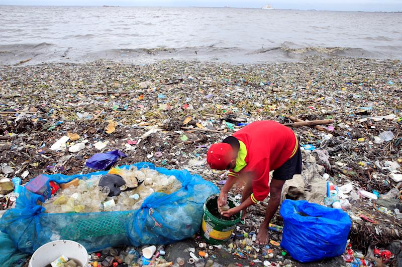 Scavengers clean plastic cups collected from rubbish washed ashore due to strong waves brought about by monsoon rains along the Manila bay, metro Manila, Philippines.(Photo: Romeo Ranoco/Reuters)