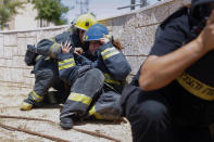 Israeli firefighters take cover as a siren sounds a warning of incoming rockets fired from the Gaza strip, in the southern Israeli town of Ashkelon, Tuesday, May 11, 2021. (AP Photo/Ariel Schalit)