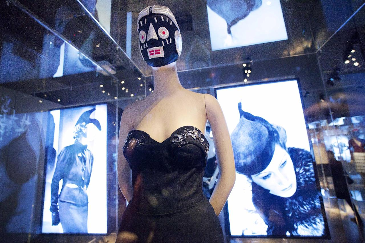 "A 2006 black wool dress by Miuccia Prada is displayed between photographs of fashions by Elsa Schiaparelli at the Metropolitan Museum of Art, Monday, May 7, 2012 in New York. The show ""Schiaparelli and Prada, Impossible Conversations,"" opens May 10 and continues through Aug. 19. (AP Photo/Mark Lennihan)"