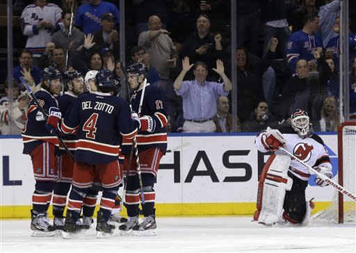 New Jersey Devils goalie Martin Brodeur, right, gets up off the ice while New York Rangers celebrate a goal by Ryan Callahan during the third period of an NHL hockey game on Sunday, April 21, 2013, in New York. The Rangers defeated the Devils 4-1. (AP Photo/Seth Wenig)