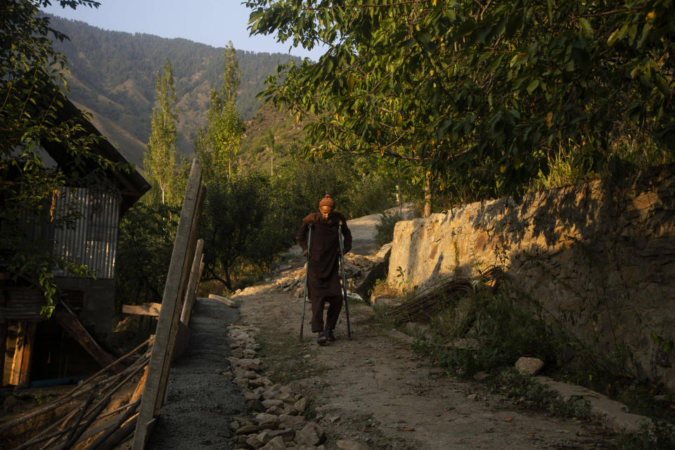 """Mohammad Yaqoob who survived a wild bear attack moves towards his home at Dardkhor village in Srinagar, Indian controlled Kashmir, Monday, Aug. 24, 2020. """"I was with cattle near my house, suddenly a bear came from the forest side and jumped on me. I was having a dog along with me that time which saved me. Unfortunately my right leg was damaged leaving me handicapped for lifetime."""", Yaqoob said. (AP Photo/Mukhtar Khan)"""