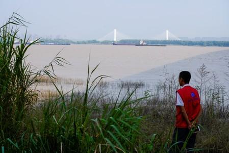 A conservationist keeps watch over porpoises at the Yangtze river near the city of Nanjing