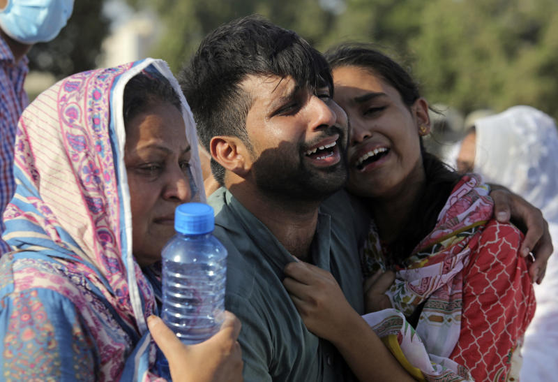 Family members and relatives of Simon Eric, who died in the crash of a state-run Pakistan International Airlines plane on Friday, mourn during his funeral in Karachi, Pakistan, Monday, May 25, 2020. (AP Photo/Fareed Khan)