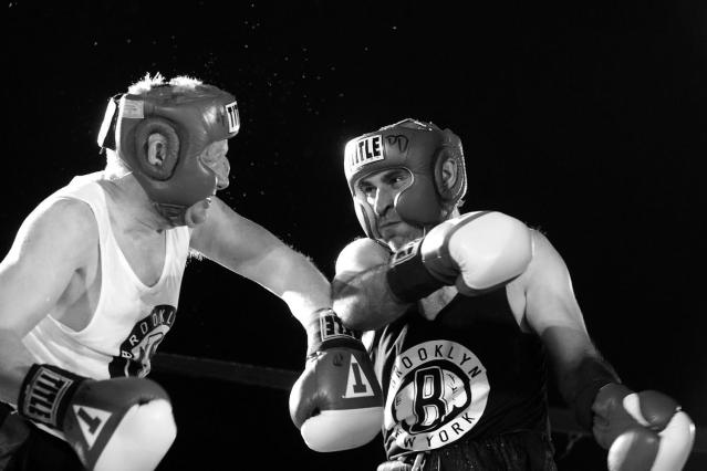 <p>Sgt. Billy Gattis gets clobbered with a punch thrown by Sgt. Russell Rodin in a battle of property clerks at the Brooklyn Smoker on Aug. 24, 2017. Gattis won the bout in a split decision. (Photo: Gordon Donovan/Yahoo News) </p>
