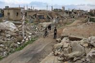 A boy rides a bicycle past a man sitting on rubble of a damaged house in the rebel held historic southern town of Bosra al-Sham, Deraa, Syria February 23, 2016. REUTERS/Alaa Al-Faqir
