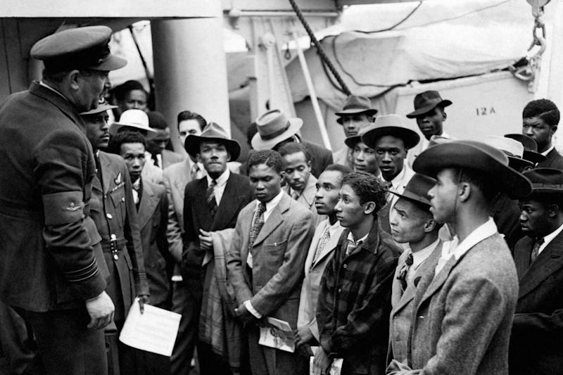Jamaican immigrants welcomed by RAF officials from the Colonial Office after the ex-troopship HMT 'Empire Windrush' landed them at Tilbury (PA)