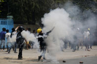 Demonstrators hurl back tear gas canisters towards police during a protest against the military coup Saturday, March 27, 2021, in Mandalay, Myanmar. Myanmar security forces reportedly killed 93 people Saturday in the deadliest day since last month's military coup. (AP Photo)