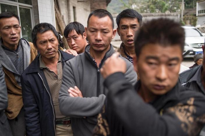 A group of men wait to speak to a journalist in Jinke village, in Pingtang county, after being told to move out of the radio silence buffer zone following the construction of the world's largest radio telescope in China's Guizhou province (AFP Photo/FRED DUFOUR)