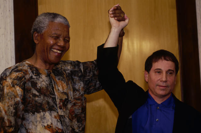 Nelson Mandela, who was elected president of South Africa in 1994, raises Paul Simon's hand in triumph. (Photo: Louise Gubb/Corbis via Getty Images)