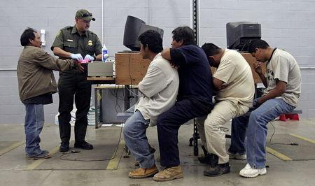 A man has his fingerprints electronically scanned by a U.S. Border Patrol agent while others wait for their turn at the U.S. Border Patrol detention center in Nogales, Arizona, May 31, 2006. REUTERS/Jeff Topping/File Photo