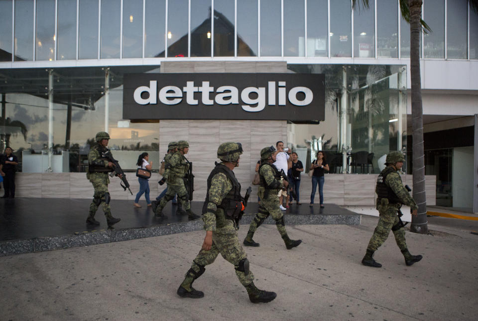 <p> Soldiers walk outside Plaza Las Americas mall following reports of gunfire in Cancun, Mexico, Tuesday, Jan. 17, 2017. Gunmen attacked the state prosecutor's office in this Caribbean resort city Tuesday, ratcheting up tensions just a day after a deadly shooting at a music festival in a nearby town. (AP Photo/Rebecca Blackwell) </p>