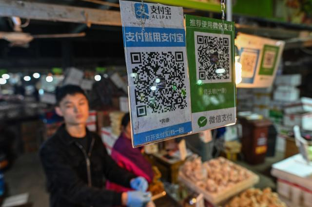 Alipay (L) and Wechat (R) QR payment codes are displayed at a market in Shanghai on October 27, 2020. (Photo by Hector RETAMAL / AFP) (Photo by HECTOR RETAMAL/AFP via Getty Images)