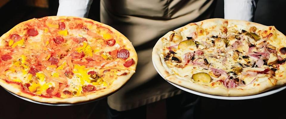 Waiter carrying two different plates with a tasty pizza. Photo with two pizza. Pizza with mushrooms and pizza with salami. Italian food. Italian restaurant.