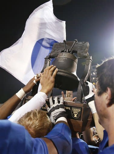 Tulsa players reach out to touch the Liberty Bowl trophy after beating Iowa State 31-17 in the NCAA college football game in Memphis, Tenn., Monday, Dec. 31, 2012. (AP Photo/Rogelio V. Solis)