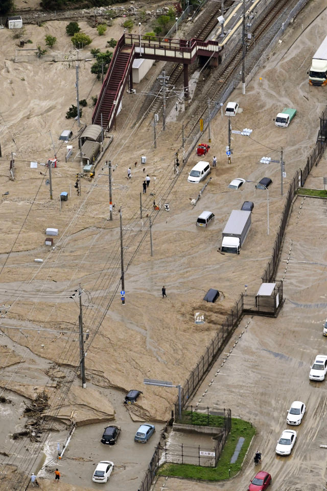 <p>Train tracks and vehicles are buried in mud caused by a heavy rain in Sakacho, Hiroshima prefecture, western Japan Saturday, July 7, 2018. (Photo: Kyodo News via AP) </p>