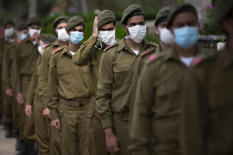 Israeli soldiers wearing protective face masks amid concerns over the country's coronavirus outbreak, stand next to graves of fallen soldiers on the eve of memorial Day in Kiryat Shaul Military Cemetery in Tel Aviv, Israel, Monday, April 27, 2020. This year the government had banned public memorial services at military cemeteries as part of its measures to help stop the spread of the virus. Israel marks the annual Memorial Day in remembrance of soldiers who died in the nation's conflicts, beginning at dusk Monday until Tuesday evening. (AP Photo/Oded Balilty)
