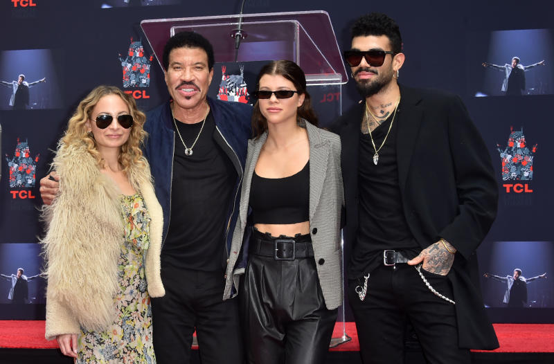 Lionel Ritchie with his children Nicole (L), Sofia and Miles (R) pose at his Hand and Footprints ceremony at the TCL Theater on March 7,2018 in Hollywood, California. / AFP PHOTO / FREDERIC J. BROWN (Photo credit should read FREDERIC J. BROWN/AFP via Getty Images)