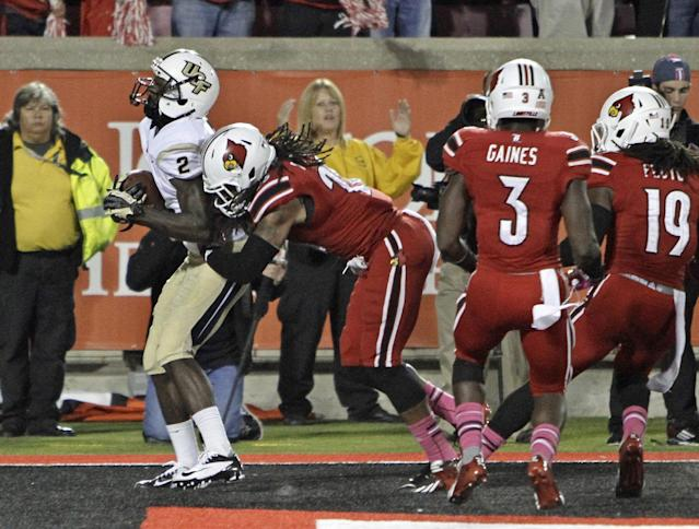 Central Florida's Jeff Godfrey (2) catches the go-ahead touchdown pass in the end zone despite the efforts of Louisville's Calvin Pryor, Charles Gaines (3) and Terell Floyd (19) in the closing minute of an NCAA college football game in Louisville, Ky., Friday, Oct. 18, 2013. Central Florida won 38-35. (AP Photo/Garry Jones)