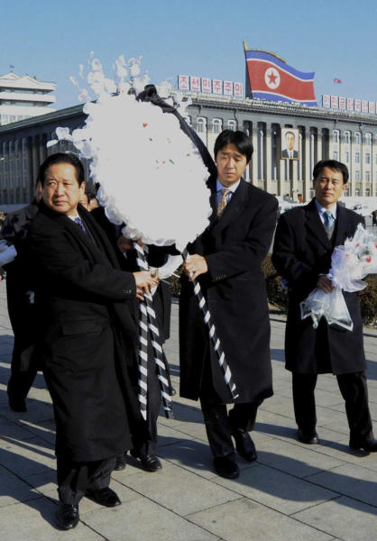"FILE - In this Dec. 24, 2011 file photo, the Rev. Hyung-jin Moon, youngest son of the Rev. Sun Myung Moon and president of the Unification Church, second from right, carries a wreath with unidentified men to lay in front of a portrait of the late Kim Jong Il at Kim Il Sung Square in Pyongyang, North Korea. Moon's U.S.-born youngest son, Hyung-jin Moon, was named the church's top religious director in April 2008. Other children run the church's businesses and charitable activities. Hyung-jin Moon told The Associated Press in February 2010 that his father's offspring do not see themselves as his successors. ""Our role is not inheriting that messianic role,"" he said. ""Our role is more of the apostles ... where we become the bridge between understanding what kind of lives (our) two parents have lived."" (AP Photo/File)"