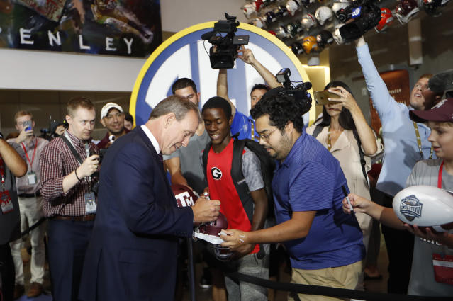 Texas A&M head coach Jimbo Fisher signs autographs for fans as he arrives for NCAA college football Southeastern Conference media days. (AP)