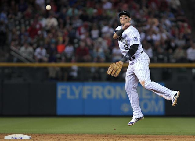 Colorado Rockies shortstop Troy Tulowitzki throws to first base to put out St. Louis Cardinals' Peter Bourjos in the sixth inning of a baseball game in Denver on Tuesday, June 24, 2014.(AP Photo/Joe Mahoney)