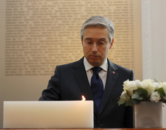 François-Philippe Champagne, Canada Minister of Foreign Affairs lights a candle in front of a plaque with the names of the victims of flight PS752, at the High Commission of Canada in London, Thursday, Jan. 16, 2020. The Foreign ministers gather in a meeting of the International Coordination and Response Group for the families of the victims of PS752 flight crashed shortly after taking off from the Iranian capital Tehran on Jan. 8, killing all 176 passengers and crew on board. (AP Photo/Frank Augstein)