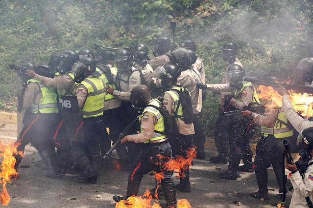 <p>Riot police officers react to fire during a rally against Venezuela's President Nicolas Maduro in Caracas, Venezuela May 1, 2017. (Photo: Christian Veron/Reuters) </p>