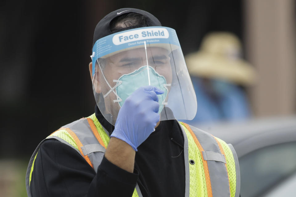 A worker demonstrates how to take a Coronavirus test at a mobile testing site at the Charles Drew University of Medicine and Science Wednesday, July 22, 2020, in Los Angeles. California's confirmed coronavirus cases have topped 409,000, surpassing New York for most in the nation. (AP Photo/Marcio Jose Sanchez)