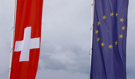 FILE PHOTO: Flags of the European Union and Switzerland flutter in the wind in Blotzheim