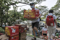 Volunteers of Keeping Hope Alive carry boxes of fresh fruit and vegetables for distribution Sunday, Oct. 4, 2020 in Singapore. Members of the volunteer group conduct weekend door-to-door visits to deliver goods or provide services to people in need. (AP Photo/Ee Ming Toh)