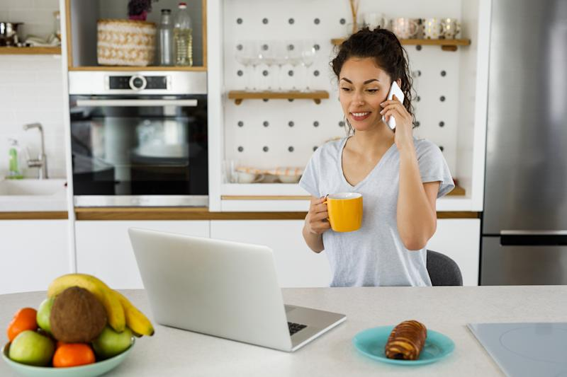 Woman working with laptop computer and smart phone at home