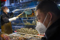 A customer wears a face mask as he shops for seafood at a market in Beijing, Saturday, March 14, 2020. The United States declared a state of emergency Friday as many European countries went on a war footing amid mounting deaths as the world mobilized to fight the widening coronavirus pandemic. For most people, the new coronavirus causes only mild or moderate symptoms, such as fever and cough. For some, especially older adults and people with existing health problems, it can cause more severe illness, including pneumonia. (AP Photo/Mark Schiefelbein)