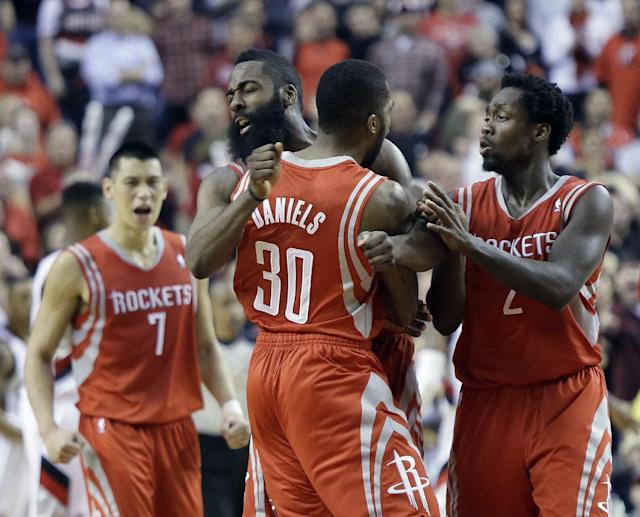 CORRECTS PERIOD TO OVERTIME - Houston Rockets guard Troy Daniel, middle, celebrates with teammates James Harden, left, and Patrick Beverley after sinking a three point shot in overtime to take the lead during Game 3 of an NBA basketball first-round playoff series against the Portland Trail Blazers in Portland, Ore., Friday, April 25, 2014. The Rockets won 121-116. (AP Photo/Don Ryan)